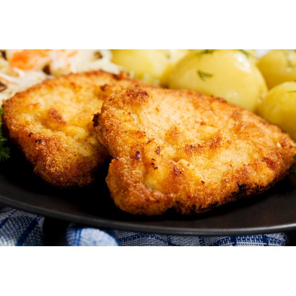 Close-up of breaded pork chops on a plate with boiled potatoes.