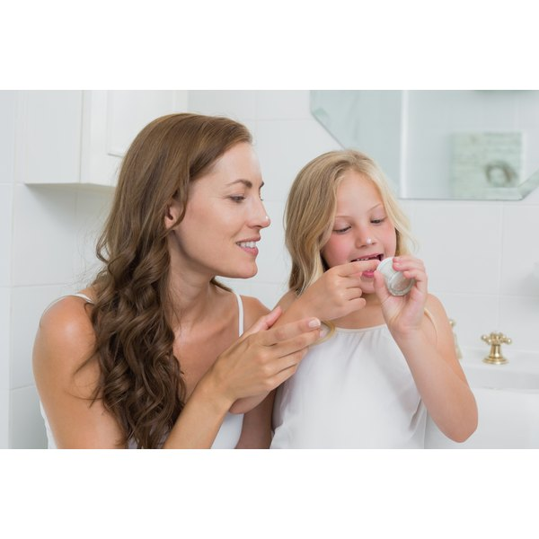 Mother and her daughter applying bag balm to their skin.