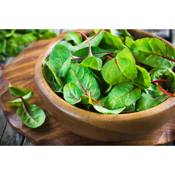 A wooden bowl of young chard leaves.