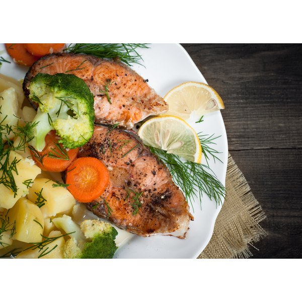 Salmon steak with vegetables and dill garnish.