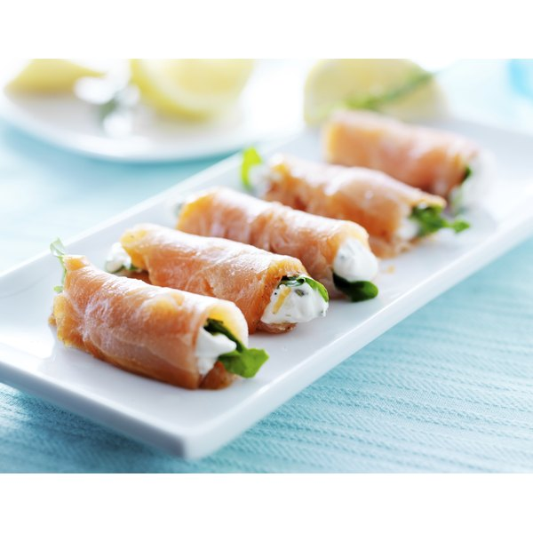 A plate of rolled up smoke salmon slices.