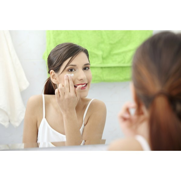 A woman applies an eye cream undeneath her eyes in the bathroom.