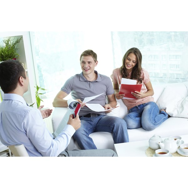 A young couple read over life insurance with their agent.
