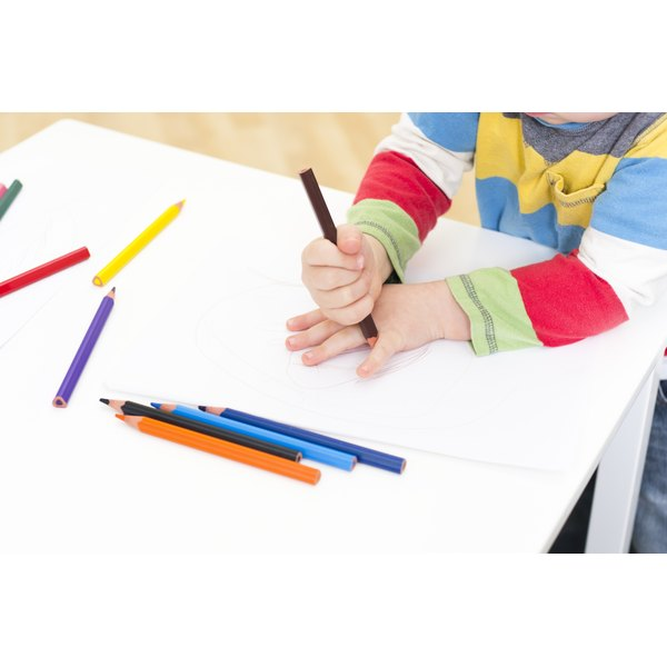 A preschooler traces his hand with a colored pencil onto a piece of paper.