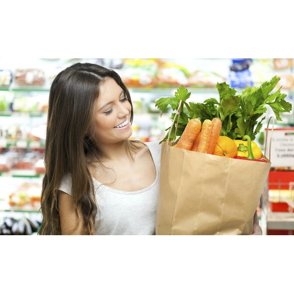 A woman is holding a bag of healthy produce.