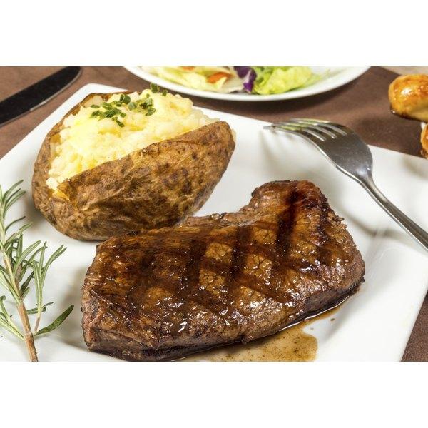 A grilled sirloin steak beside a baked potato.
