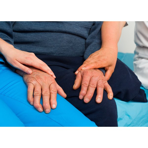 The hands of a caregiver touch an elderly patient's hands