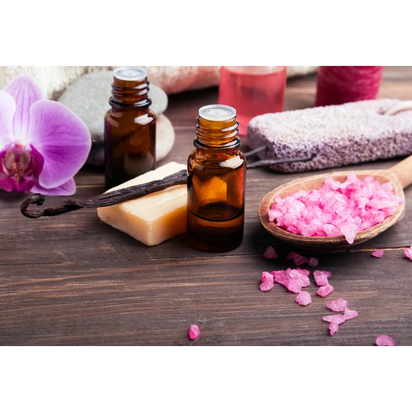 Bottles of vanilla essential oil on a table with spa products, orchid petals and seed pods.