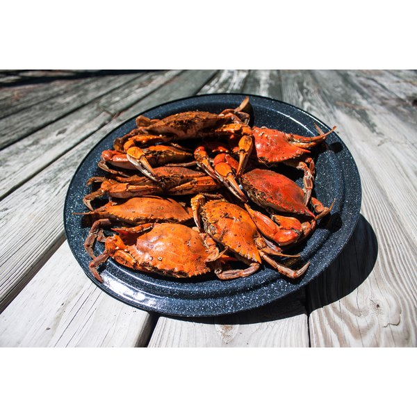 A plate of blue crab sits on a wooden dock.