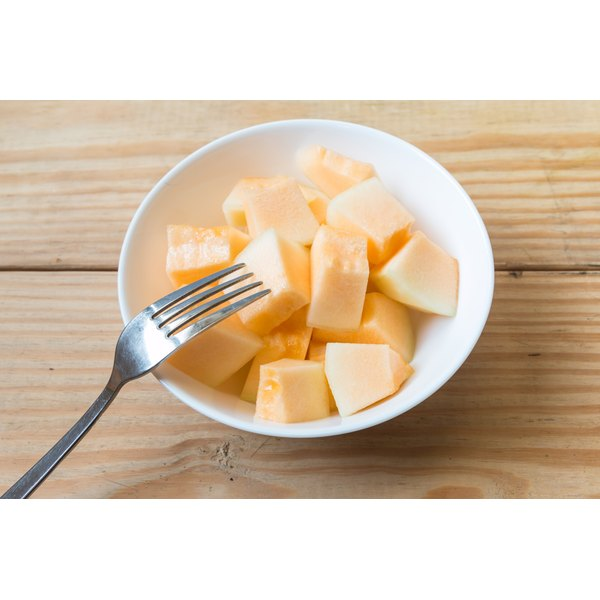 A bowl of cubed cantelope melon and a fork.