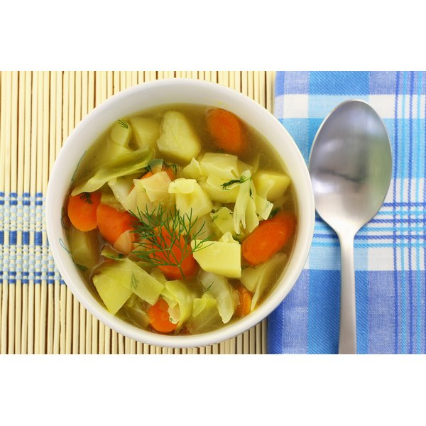 A bowl of cabbage soup on a bamboo place mat.