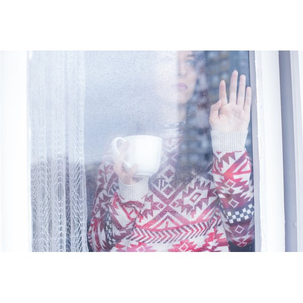 Woman staring out window drinking coffee with hand pressed up against window.