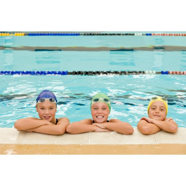 Three children wearing various colored swim caps.