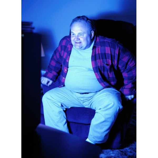 Overweight man watching tv.