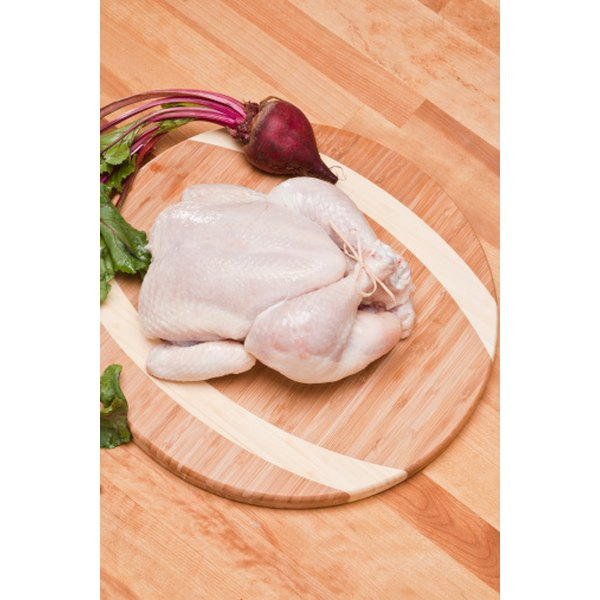 Whole chicken on cutting board.
