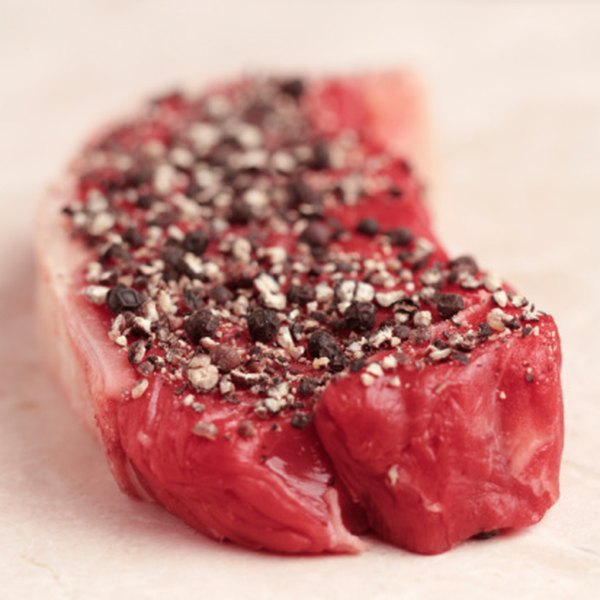 Coat your strip steaks with seasonings such as pepper and kosher salt.