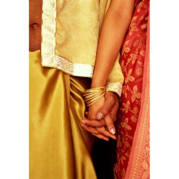 The man on the left is wearing a formal gold dhoti tied around his waist.