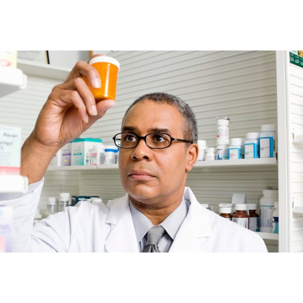 Pharmacist looking at a prescription bottle