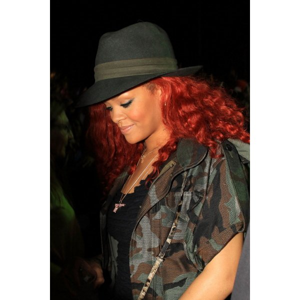 Rihanna sports a dark gray fedora matching her outfit.