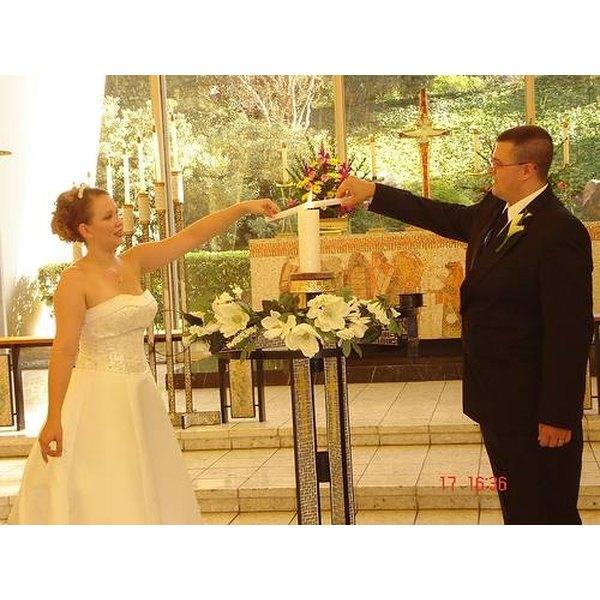 A wedding couple lighting the unity candle.