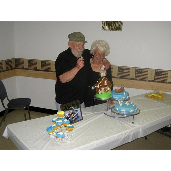 A couple cutting their 60th anniversary cake.