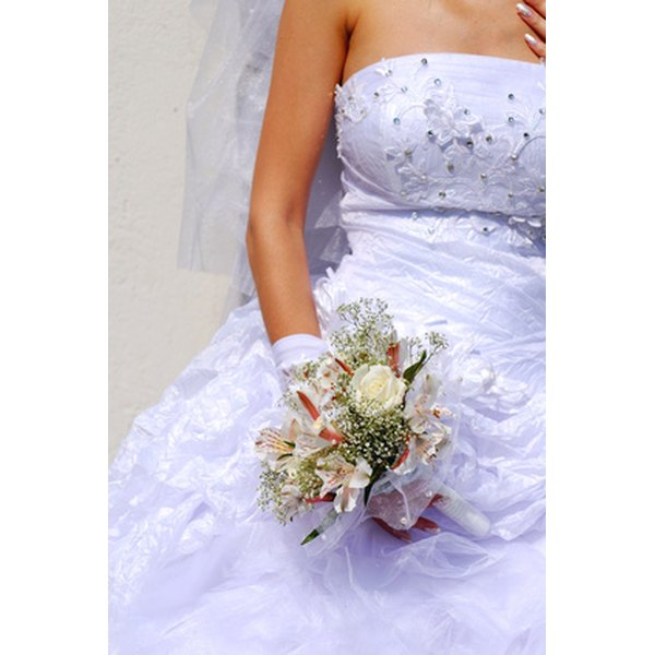 Trying to hide a stain on a wedding dress with a bouquet? Cleaning the stain is a better solution.