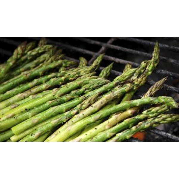 Asparagus spears cooking on a grill.