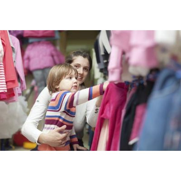 A two-year old girl picks out clothing in a closet with her mother.