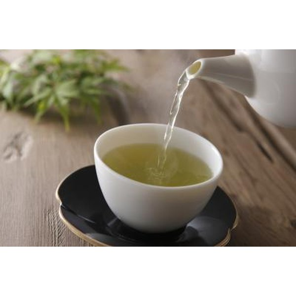 A cup of green tea being poured from a tea pot.