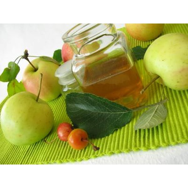 Apple cider vinegar surrounded by apples and fruit.