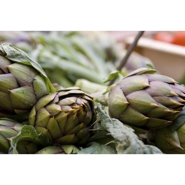 Fresh green artichokes at an outdoor market.