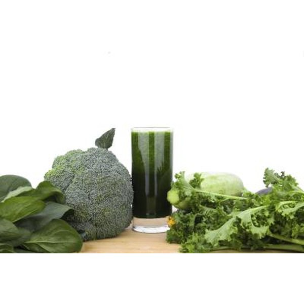 Green juice with green vegetables on a table.