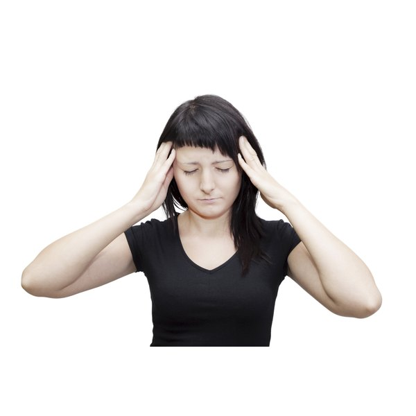 A teenager in a black top holds her head as she suffers from tinnitus.