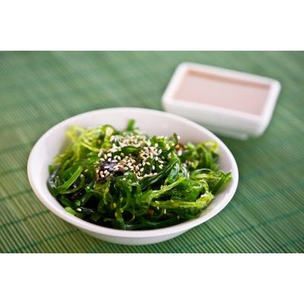 Seaweed salad with a side of dressing on a bamboo placemat.