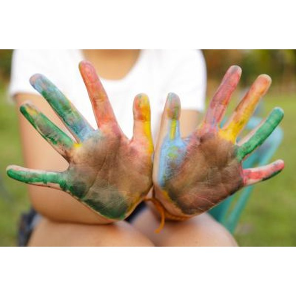 A girl holds up her hands, stained with paint colors.