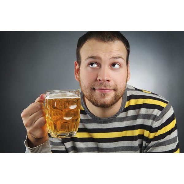 A guy raises his glass of beer as he contemplates drinking it...