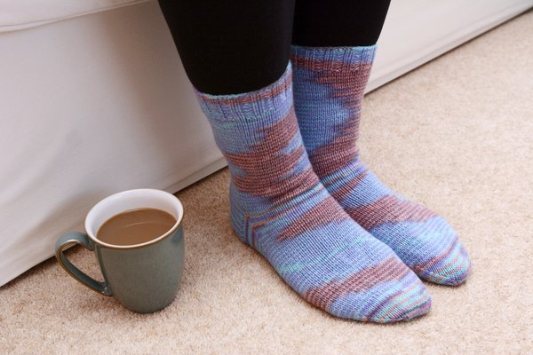 A women's knitted socks on a carpet.