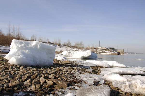 Chunks of ice and snow on the rocks of a river bed.