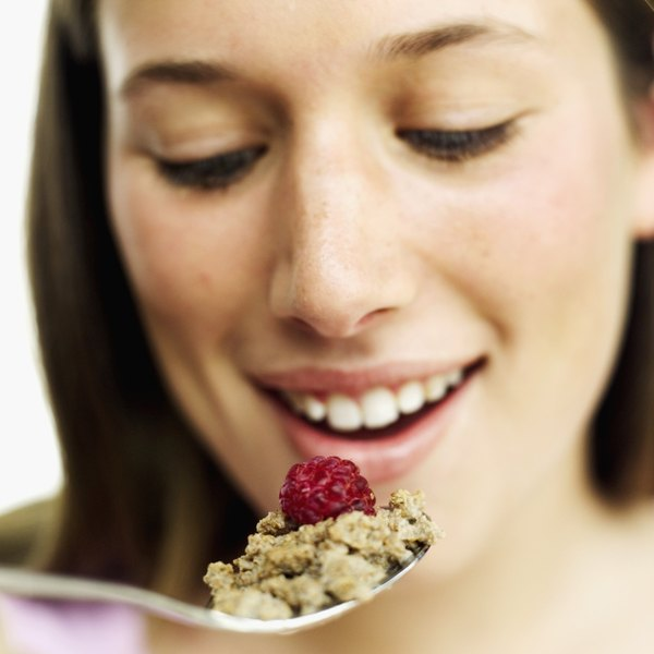 Whole-grain cereal combined with raspberries and milk provides a healthy serving of carbohydrates.