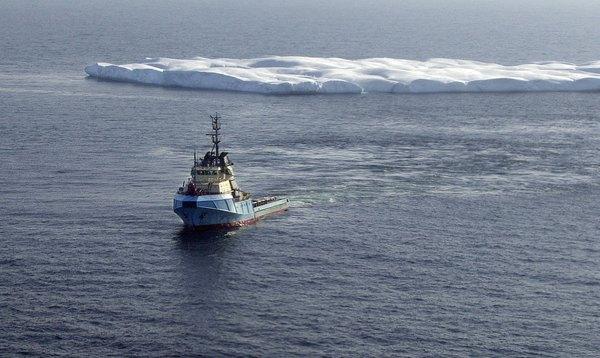 A tugboat tows an iceberg off a possible collision course with an oil drilling platform