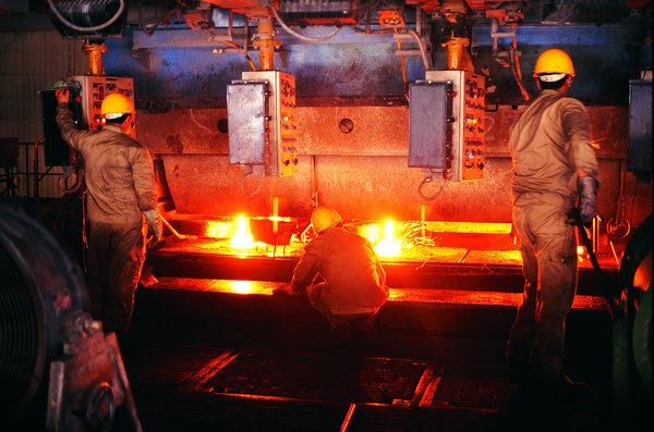 Foundry workers testing steel