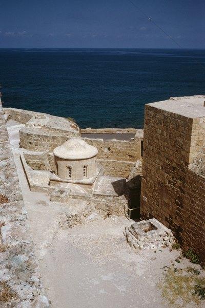 Vista parcial e angular de uma antiga fortaleza no Chipre, com o Mediterrâneo ao fundo