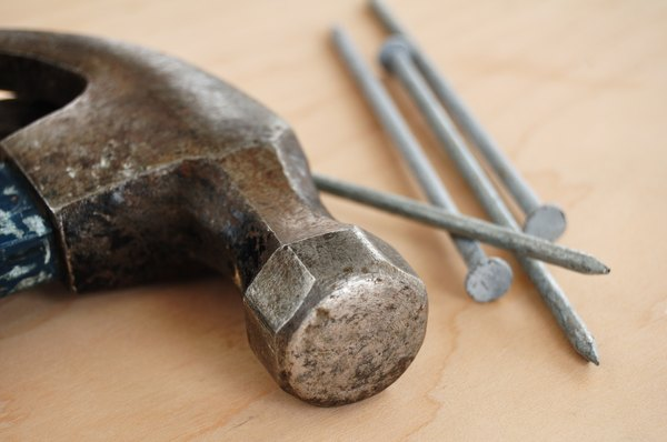 Close-up of a claw hammer lying next to several nails