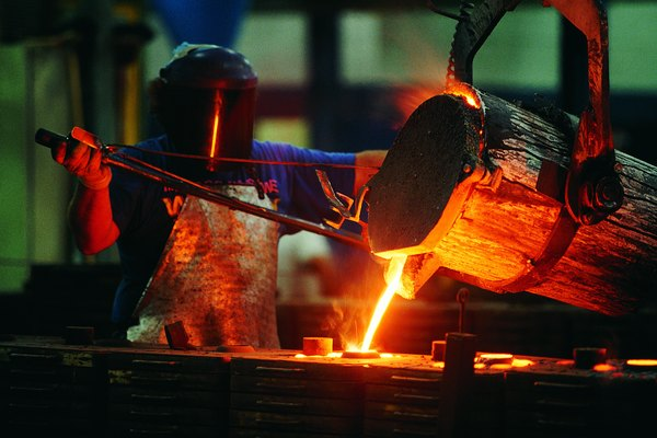Foundry worker pouring liquid steel