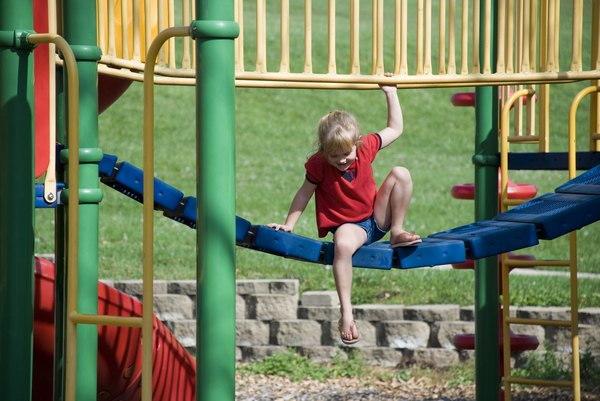 A child playing on a colorful jungle gym at the park.