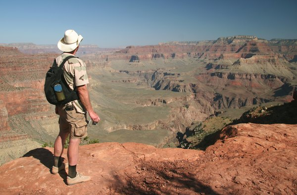 A man stands on the edge of a rock to view the Grand Canyon in Arizona.