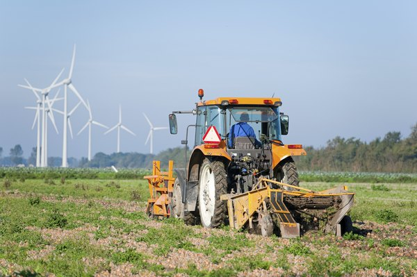 A farmer drives a tractor over a field.
