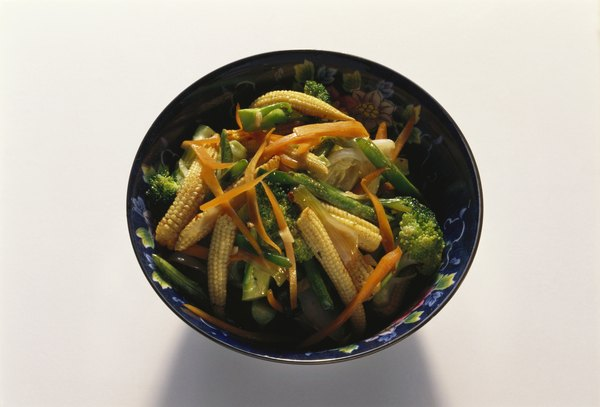 Healthiest foods to eat at thai restaurants woman stir fried vegetables make for a healthy thai food dish forumfinder Choice Image