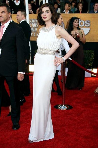 Como el cuello adornado de Kim Kardashian, Anne Hathaway aumenta el lujo con un escote y una cintura detallados.