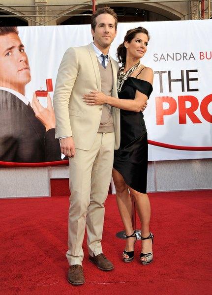 O ator Ryan Reynolds ao lado de Sandra Bullock, usando um terno cáqui